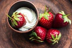 Ny jordgubbe med vispgrädde på en mörk platta Royaltyfri Bild