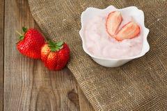 Ny jordgubbe med yoghurt i den vita bunken på träbakgrund Royaltyfri Foto