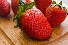 Ny jordgubbe som är saftig på trätabellen på ett kök arkivfoton