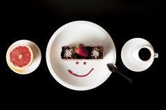 Ny jordgubbekaka på den vita plattan med koppen kaffe och grapefrukten Royaltyfria Bilder