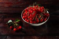 Ny körsbär på plattan på träbakgrund nytt moget för Cherry Cherry en för platta white sött Arkivbild