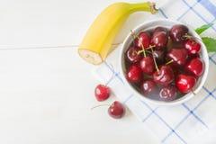 Ny körsbär på plattan på trävit bakgrund nytt moget f?r Cherry Cherry en f?r platta white s?tt arkivfoto