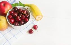 Ny körsbär på plattan på trävit bakgrund nytt moget f?r Cherry Cherry en f?r platta white s?tt royaltyfri foto