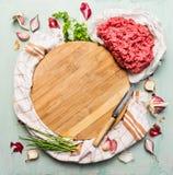 Ny köttfärs med nya örter och kryddor runt om träskärbräda Arkivfoto