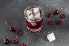Ny k?rsb?rsr?d coctail En coctail med gin eller vodka, körsbärsröd sirap och stycken körsbär och is royaltyfri bild