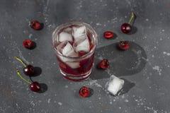 Ny k?rsb?rsr?d coctail En coctail med gin eller vodka, körsbärsröd sirap och stycken körsbär och is royaltyfria bilder