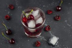 Ny k?rsb?rsr?d coctail En coctail med gin eller vodka, körsbärsröd sirap och stycken körsbär och is arkivbilder