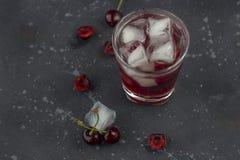 Ny k?rsb?rsr?d coctail En coctail med gin eller vodka, körsbärsröd sirap och stycken körsbär och is arkivbild