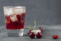 Ny k?rsb?rsr?d coctail En coctail med gin eller vodka, körsbärsröd sirap och stycken körsbär och is royaltyfri foto