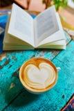 Ny kaffe och bok på en trätabell Royaltyfri Fotografi