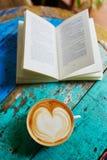 Ny kaffe och bok på en trätabell Arkivfoton