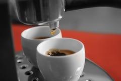 Ny kaffebryggare som häller ny espresso in i två koppar, Arkivfoton