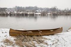 Ny kanot som svävar på det lugna vattnet i vintersolnedgång Arkivbilder