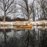 Ny kanot som svävar på det lugna vattnet i vintersolnedgång Royaltyfri Bild