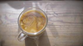 Ny kräm hällde in i ett svart starkt kaffe Mörka atmosfäriska kaféer, solig eftermiddag stock video