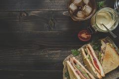 Ny läcker klubbasmörgås, såser och drink på trädaen arkivbilder