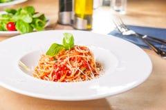 Ny lagad mat italiensk spagetti, pasta med marinara eller tomatsås som dekorerades med basilika på den vita plattan, tjänade som  royaltyfria bilder