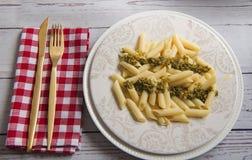 Ny lagad mat pasta med sås tjänade som på den vita plattan med gaffeln och kniven på tabellen Arkivfoton