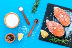 Ny laxbiff med kryddor, rosmarin, citron för att laga mat sund mat på bästa sikt för blå bakgrund arkivbild