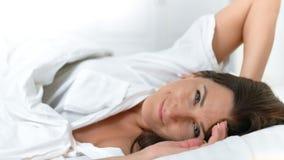 Ny le kvinna för stående som hemma vaknar upp på morgonen i hemtrevlig vit säng lager videofilmer