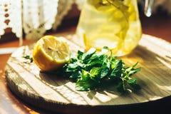 Ny lemonad i krus med den gula citronen och mintkaramellen på träkökbakgrund Vattendetox Arkivbild