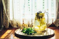 Ny lemonad i krus med den gula citronen och mintkaramellen på träkökbakgrund Vattendetox Arkivbilder