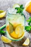 Ny lemonad med mintkaramellen, citronen och is i den glass kruset på träbakgrund Sommardrinkar och coctailar royaltyfria foton