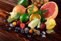 Ny limefrukt, ananas, jordgubbar, nya gröna sidor av mintkaramellen, blåbär, druvor och is på ett suddigt färgrikt Royaltyfria Bilder