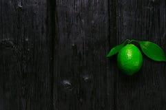 Ny limefrukt på den brände till kol träbakgrunden Arkivbild