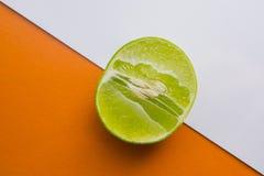 Ny limefrukt som är halv på den orange och vita bakgrunden arkivfoton