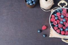 Ny mörk bild för hallon och för blåbär med kopieringsutrymme på vänstersida Nya frukter, bär i en gammal kopparkopp, bunke Mörk v arkivbild