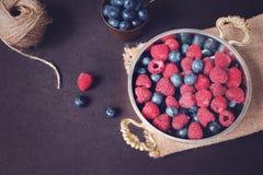 Ny mörk bild för hallon och för blåbär med kopieringsutrymme på vänstersida Nya frukter, bär i en gammal kopparkopp, bunke Mörk v royaltyfri bild