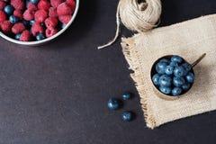 Ny mörk bild för hallon och för blåbär med kopieringsutrymme på vänstersida Nya frukter, bär i en gammal kopparkopp, bunke Mörk v royaltyfri fotografi