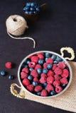Ny mörk bild för hallon och för blåbär Nya frukter, bär i en gammal kopparkopp, bunke Mörker utformat materielfoto, svart B arkivfoton