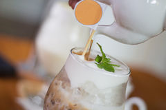 Ny med is kaffe och kruka med orange cirkellogo Arkivfoto