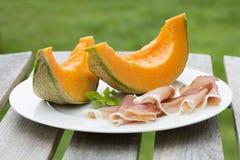 Ny melon med serranoskinka i platta Arkivfoto