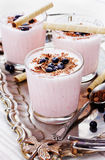Ny milkshake, yoghurten, efterrätten, smoothie med den dekorerade jordgubben grated choklad och djupfrysta blåbär Royaltyfri Fotografi