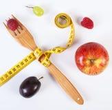 Ny mogen frukter och gaffel med cm på vit bakgrund Arkivfoto