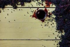 Ny mogen violett svarta fläderbär och fläderbärfruktsaft på den lantliga grå färggulingtabellen royaltyfria bilder