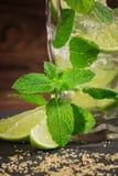 Ny mojitococtailnärbild Sommardryck med mintkaramellen, iskuber och limefruktsegment, på träbakgrunden Royaltyfri Foto