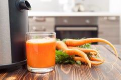 ny morotfruktsaft från unga morötter på tabellen Royaltyfri Foto