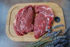 Ny nötköttbiff på en skärbräda och lavendel förgrena sig Royaltyfri Bild