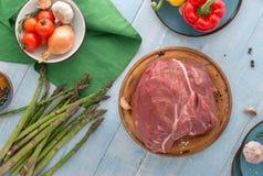 Ny nötköttfläskkarré på den blåa trätabellen med olik vegeta arkivfoton