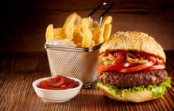 Ny nötkötthamburgare med korgen av pommes frites royaltyfri bild
