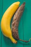 ny och rutten banan på träbakgrund Arkivbilder
