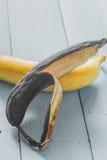 ny och rutten banan på träbakgrund Royaltyfri Fotografi