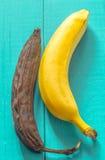 ny och rutten banan på träbakgrund Royaltyfria Bilder
