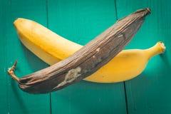 ny och rutten banan på träbakgrund Arkivbild