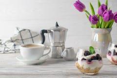 Ny och sund frukost med granola, yoghurt, kaffe och den purpurfärgade tulpanbuketten arkivbild