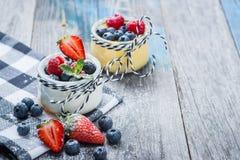 Ny och sund naturlig yoghurt med bär på trätabellen Arkivfoton